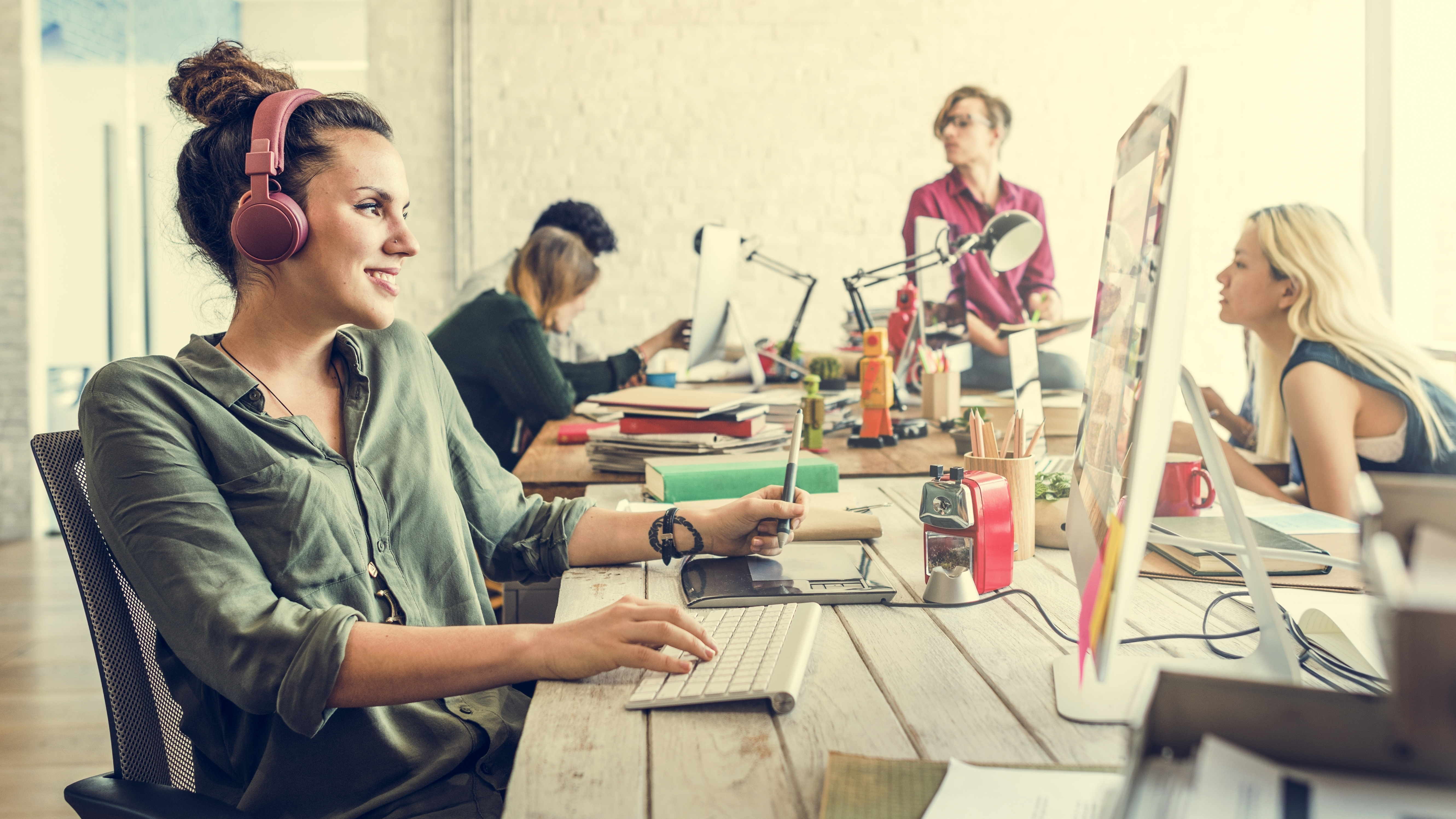 Working in Shared Workspace - Image of a Girl with Headphone and Three Other Coworkers